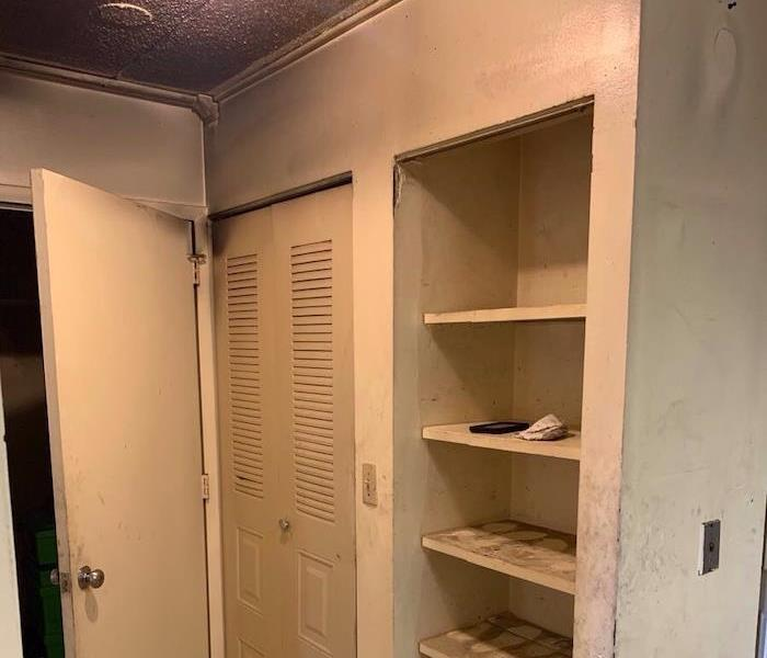 Bathroom with smoked damaged shelves and ceiling with flooring removed