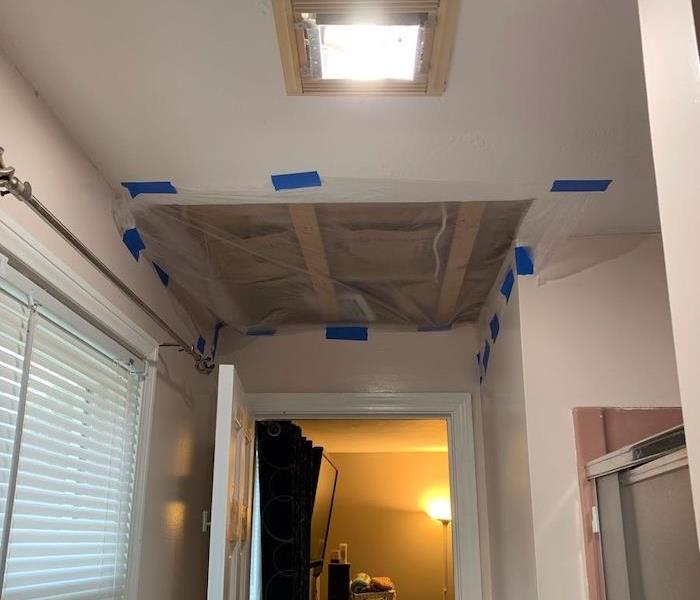 Bathroom ceiling with plastic over cut away hole in the ceiling
