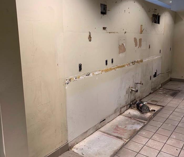 Cafeteria room with sinks and cabinet removed with mold on sheetrock