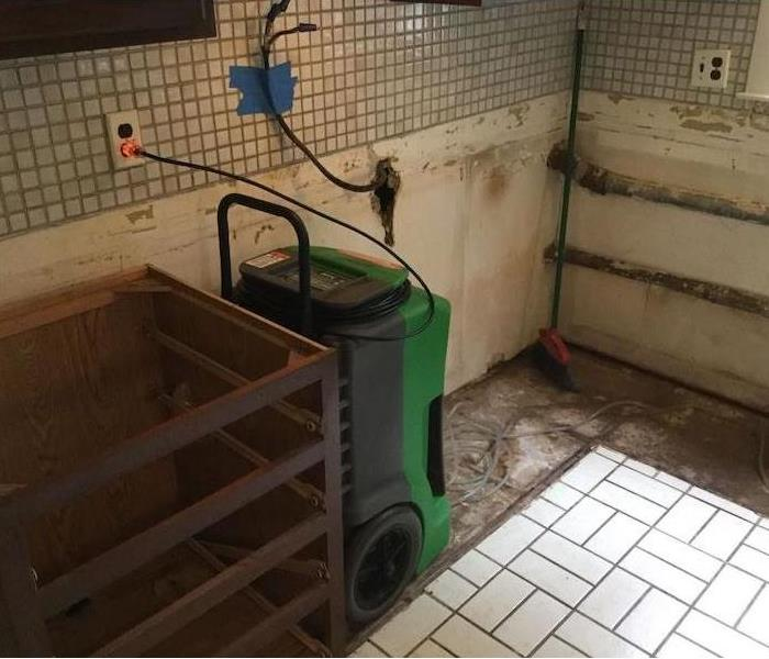 Kitchen with tile floor exposed pipes and SERVPRO drying equipment