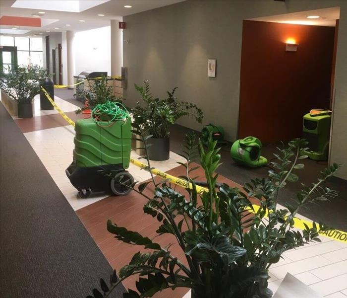 Green SERVPRO drying equipment running in a Hotel lobby with commercial water damage