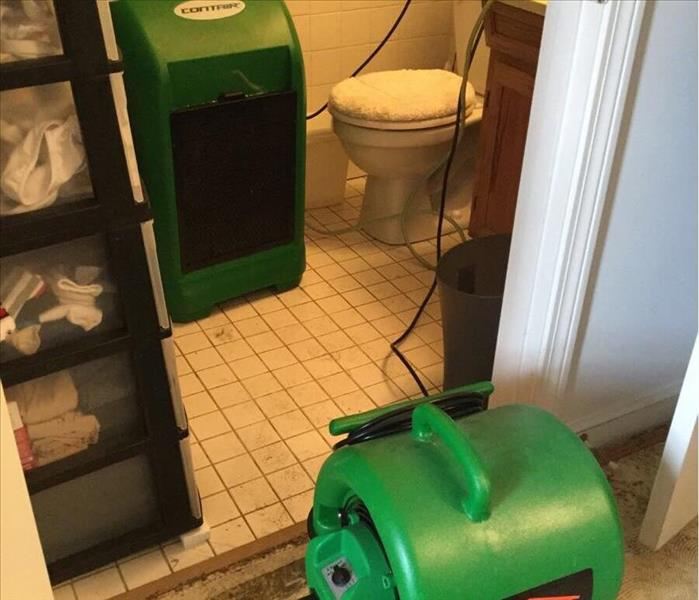 Dehumidifier and air mover drying out wet bathroom