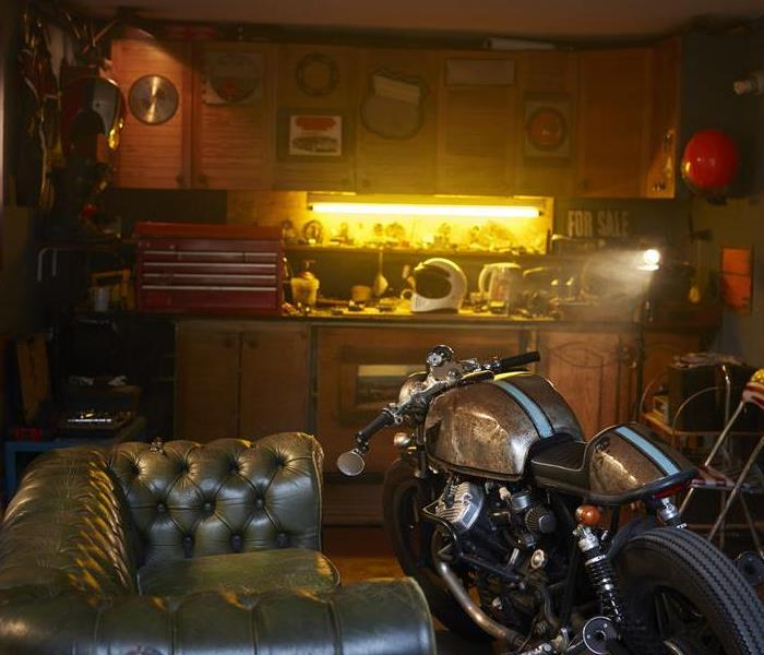 A garage with a green leather couch and motorcycle in it, with a tool box.