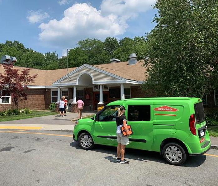 servpro sales car with agent in front of building