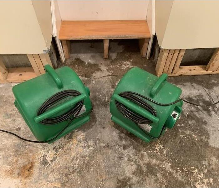 SERVPRO equipment at work. Wall with flood cuts.
