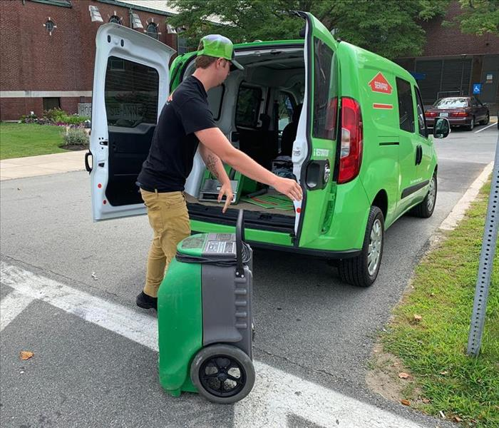 Tech off-loading dehumidifier from a small SERVPRO vehicle