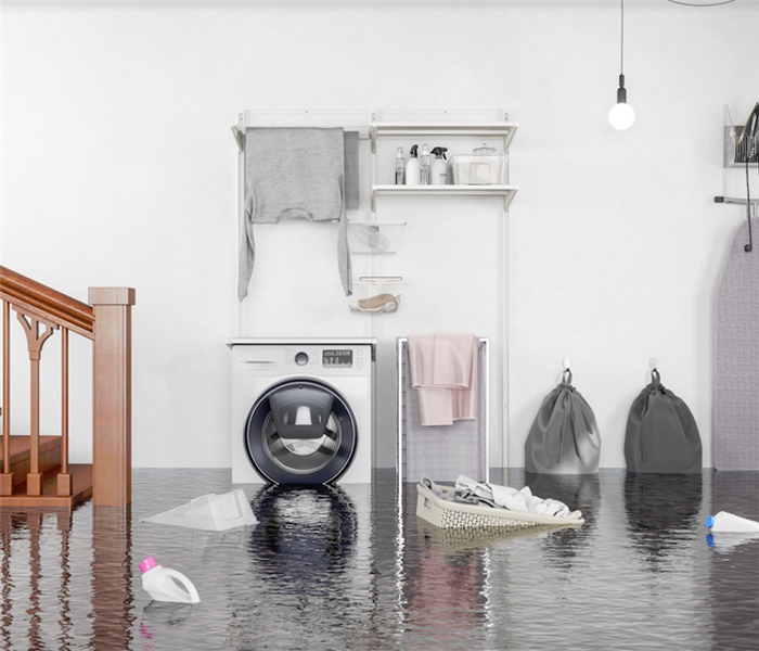 a flooded laundry room with buckets and clothes floating everywhere