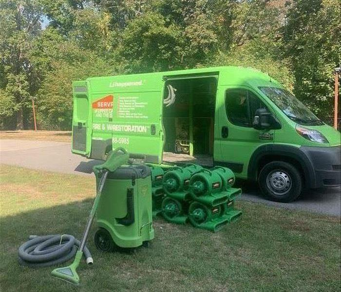 Green SERVPRO service vehicle with equipment outside the residence.
