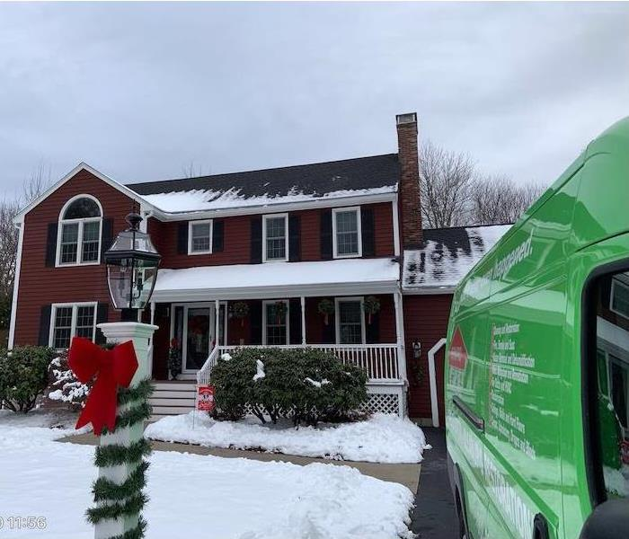 Red brick house covered in snow with a green SERVPRO van in the driveway